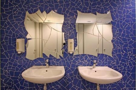 De spiegels zijn ook in de wand getegeld. In deze speciale situatie hebben leerling-tegelzetters onder begeleiding van hun leermeesters deze mozaïeken gemaakt.